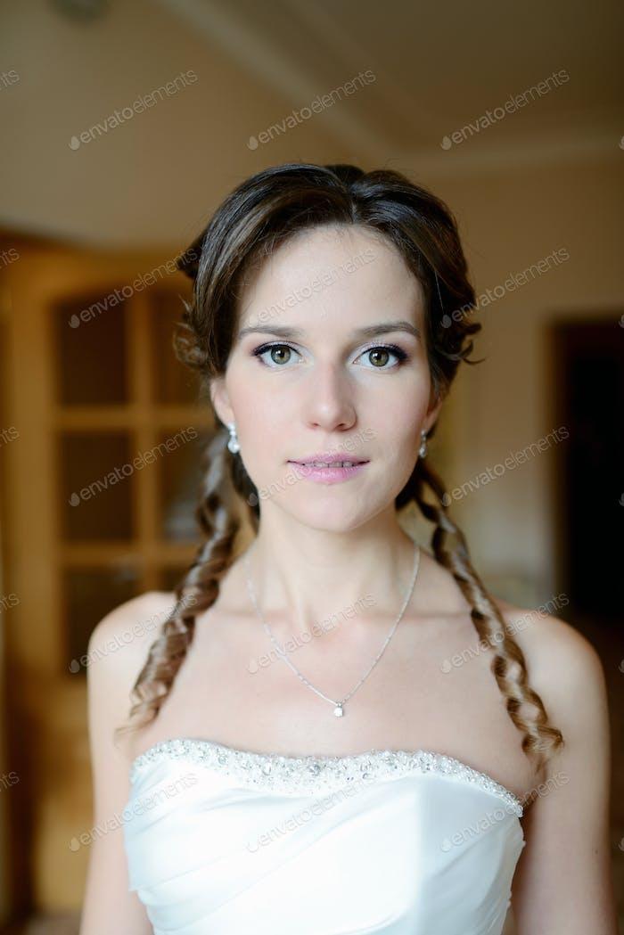 Novia de belleza en vestido de novia con velo de encaje en el interior