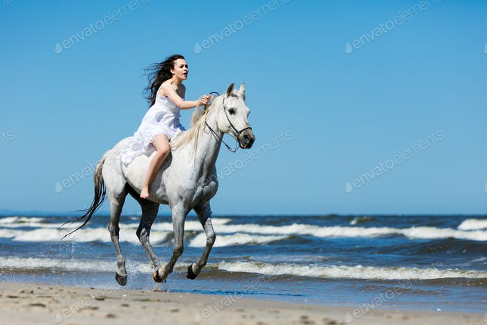 Girl storming through the beach on a white horse