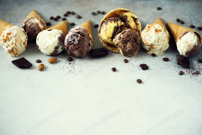 Chocolate and coffee ice cream in waffle cone with coffee beans on grey stone background. Summer