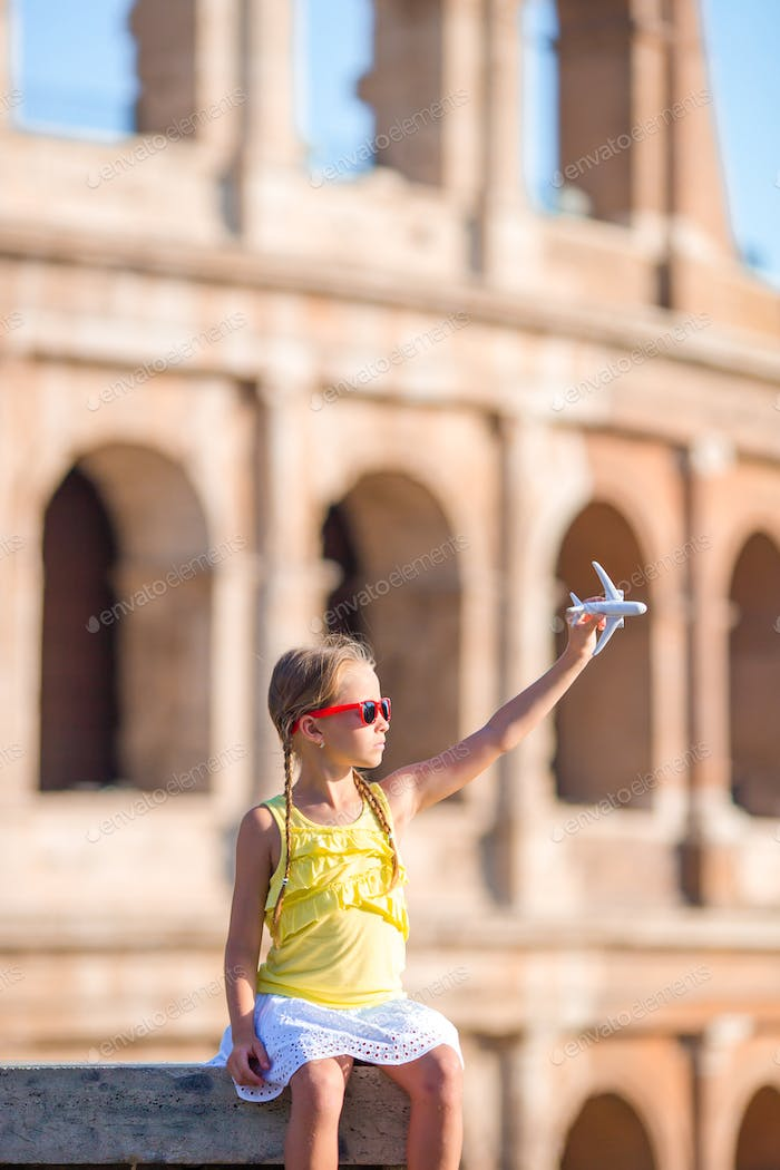 Adorable girl with small toy model airplane background Colosseum in Rome, Italy