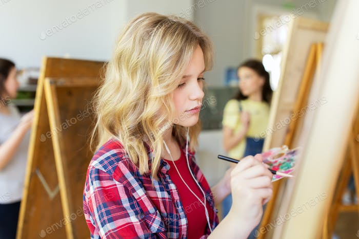 student girl with easel painting at art school