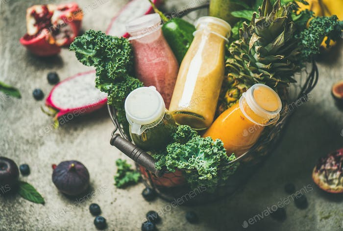 Colorful smoothies in bottles with fruits in basket, selective focus