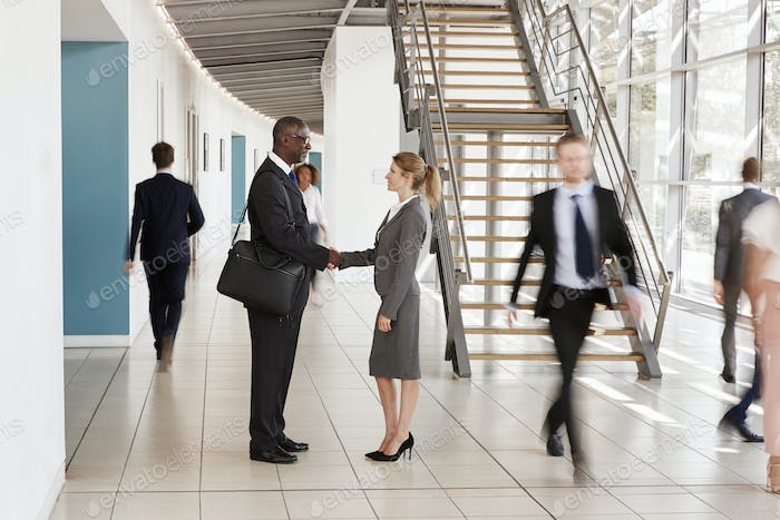 Businessman and woman shaking hands in a busy modern lobby