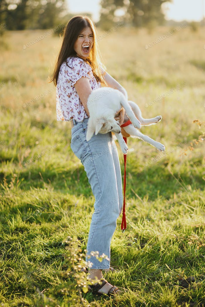Girl holding playful adorable fluffy puppy, hilarious moment