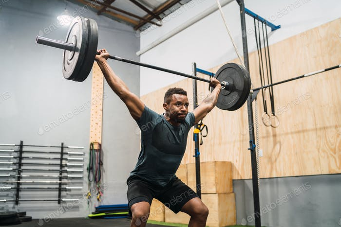 Crossfit athlete doing exercise with a barbell.