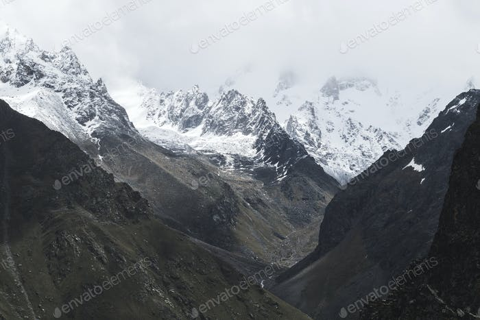 Snow mountain peaks of Caucasus mountains in cold cloudy weather, Elbrus Region.