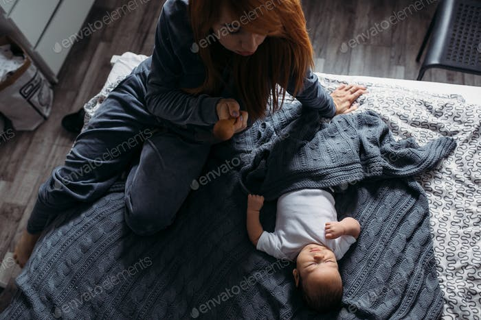 Mother with her baby in bedroom