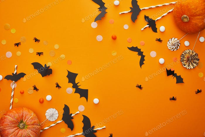 top view of pumpkin, bats and spiders with confetti on orange background, Halloween decoration