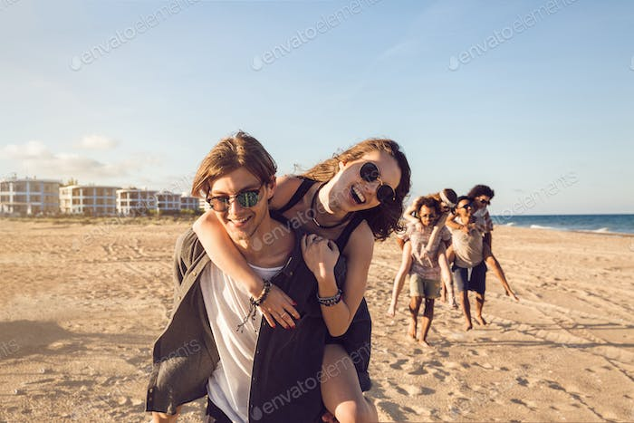Three young men giving their girlfriends piggyback rides