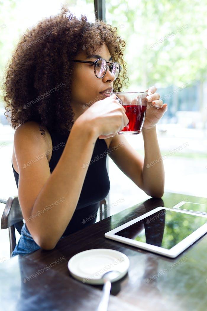 Schöne junge Frau trinkt roten Tee in einem Café.