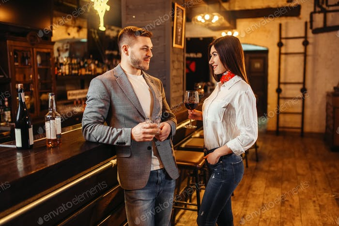 Man and woman drinks red wine at bar counter