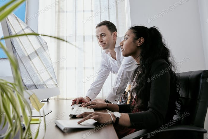 Man standing by a woman looking at a computer screen,