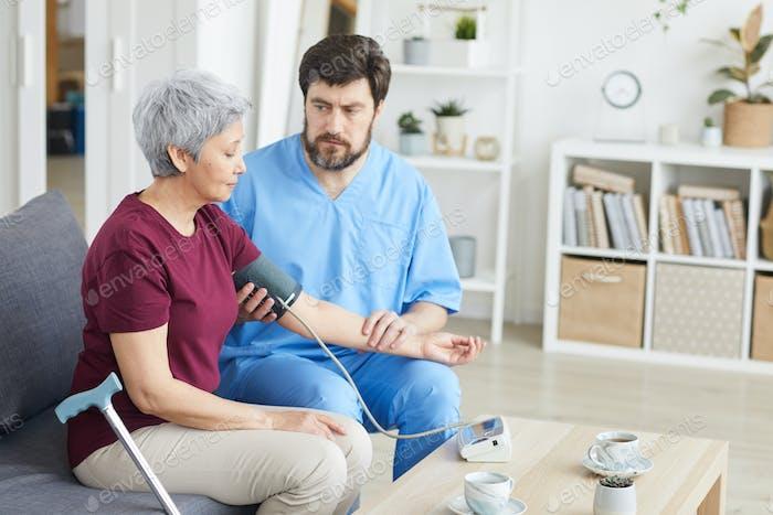 Doctor measuring his patient's blood pressure