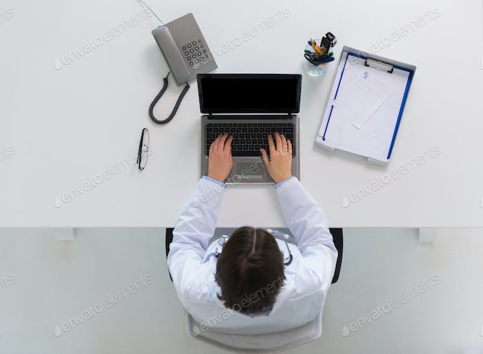 woman doctor typing on laptop at clinic