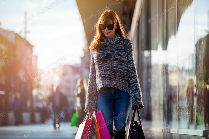 Urban scene, Woman walks on street with shopping bags