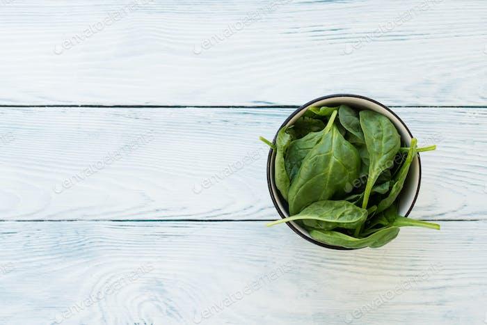 Крупным планом листья шпината на белом деревянном столе