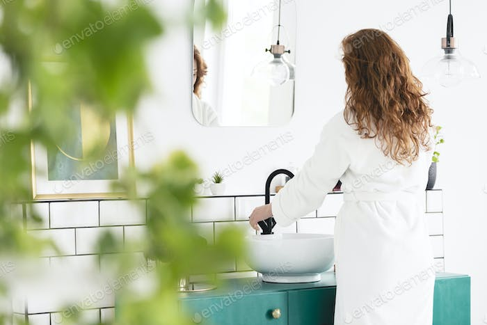 Woman in white dressing-gown washing hands in bathroom interior