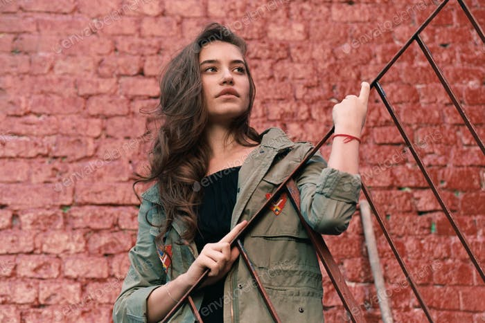 fashionable young female stand on steel stairs