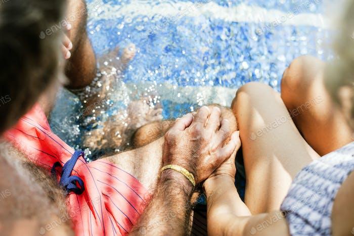 Seniorenpaar Hand am Schwimmbad