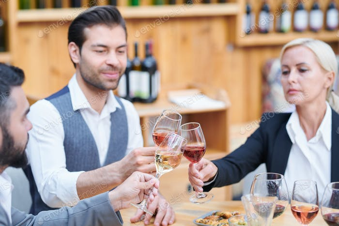 Group of contemporary winery experts clinking with glasses of various wine