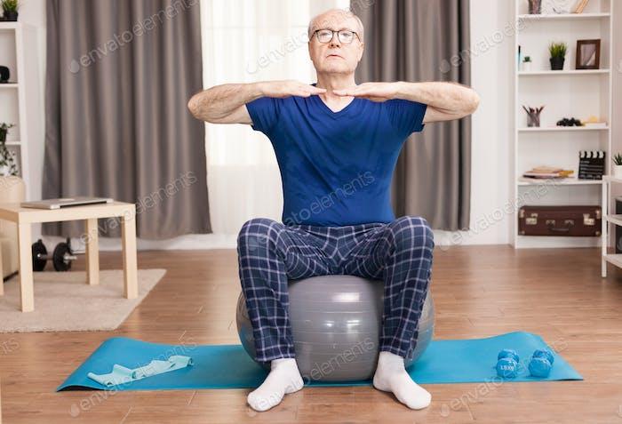 Senior man training on stability ball