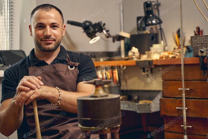 Smiling jeweler sitting in front of the anvil