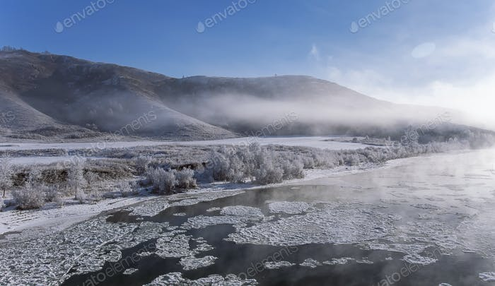 foggy winter landscape frosty morning over the river in hoarfrost on the shores of Altai mountain