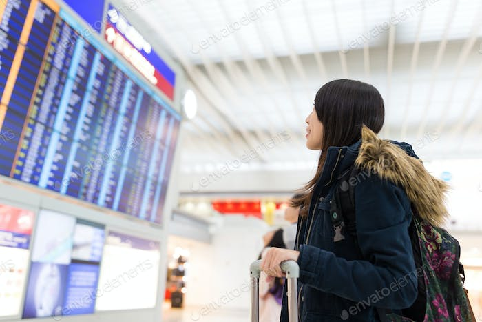 Woman looking at information board and checking her flight