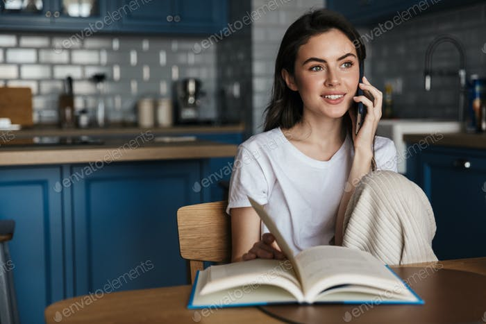 Attractive young brunette woman reading a book