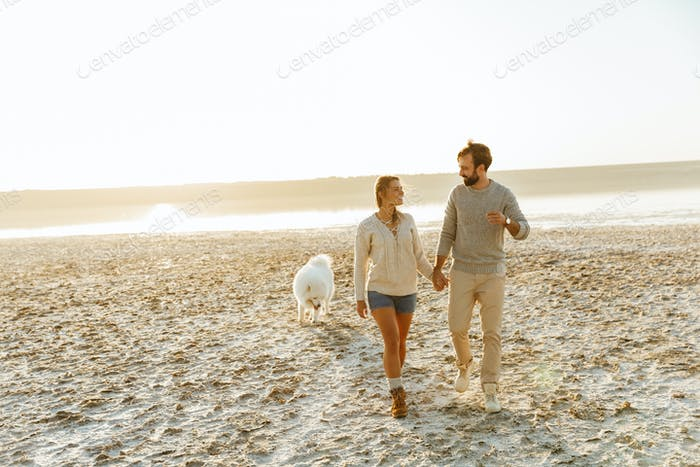 Cheerful young couple walking at the beach