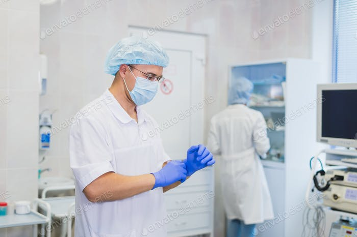 Young doctor during preparation for operation. Assistant of surgeon wearing surgical mask in