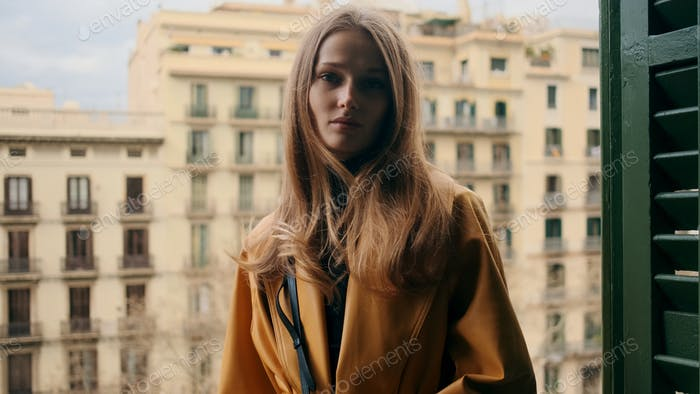 Gorgeous stylish girl thoughtfully standing on balcony with beautiful view on the center