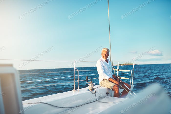 Mature man enjoying a sunny day sailing his boat