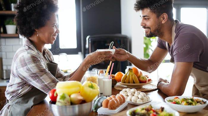 Happy couple preparing healthy food in kitchen