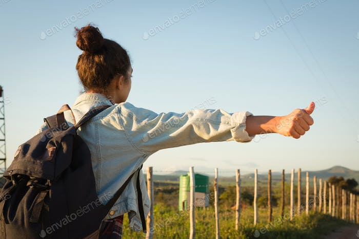 Woman hitchhiking on a sunny day