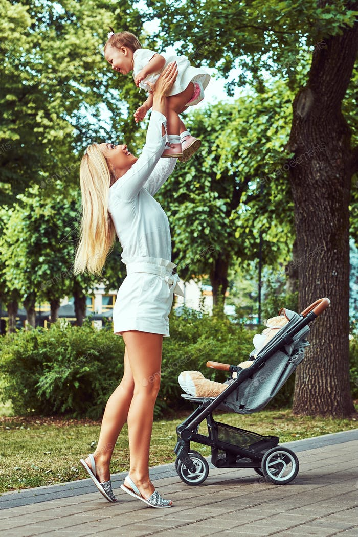 Family and people concept - happy blonde mother with his little daughter in the park.