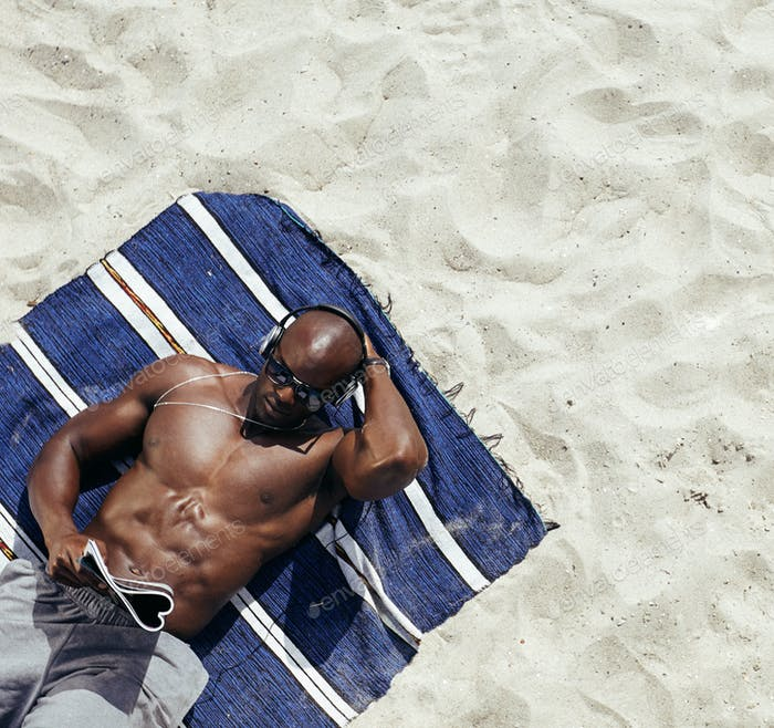 Muscular young man reading magazine on beach
