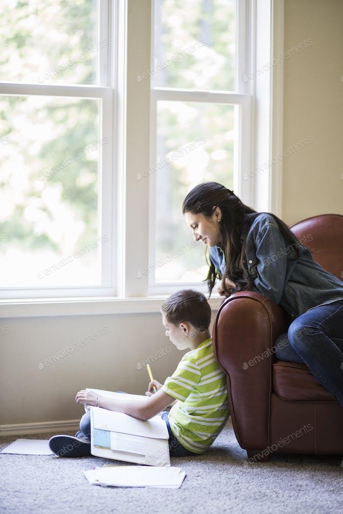 Un joven que trabaja en casa con su madre sentada cerca.