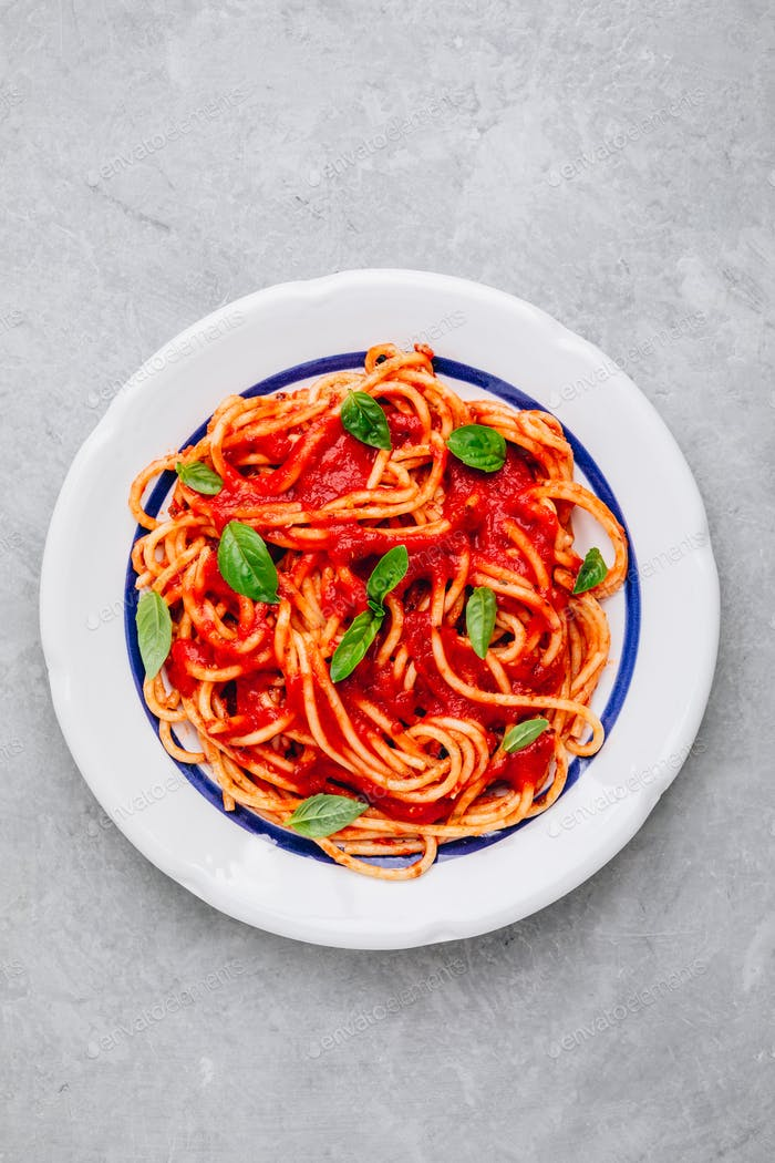 Italian spaghetti pasta with tomato sauce, basil and parmesan cheese
