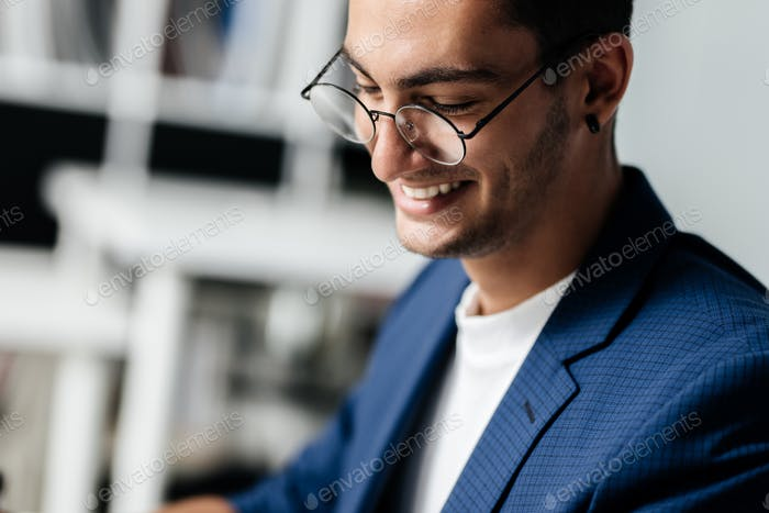Dark-haired young architect in glasses dressed in blue checkered jacket smiles