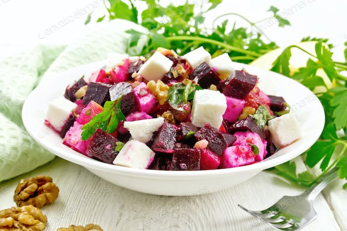 Salad with beetroot and apple in plate on board