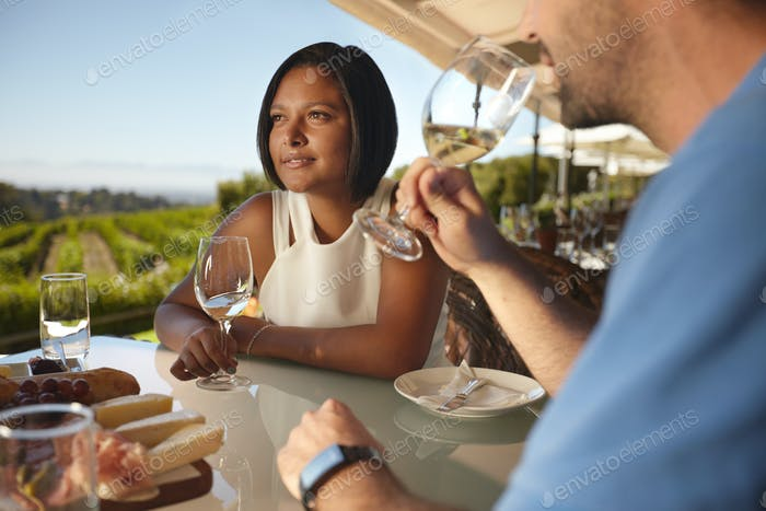 Couple on vacation in outdoor wine bar restaurant.