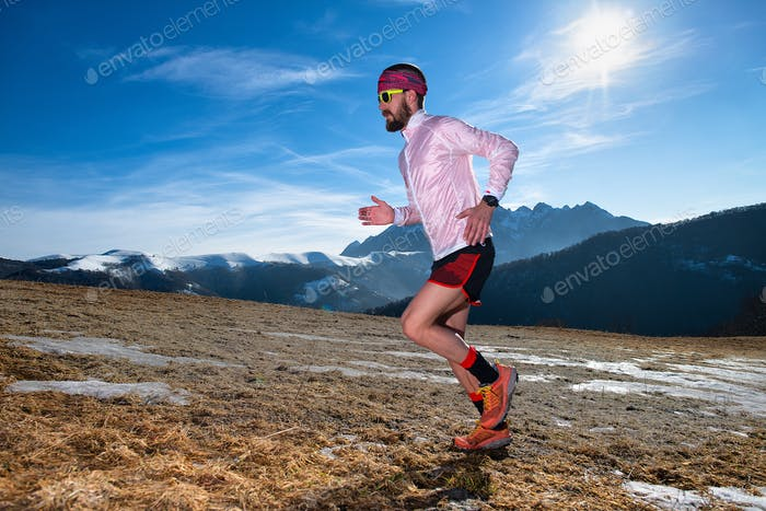 Mountain runner in action uphill on slippery ground