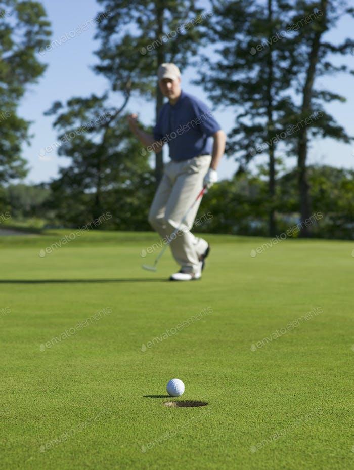 Golfer feiert einen Puttt mit Fokus auf Ball und Loch
