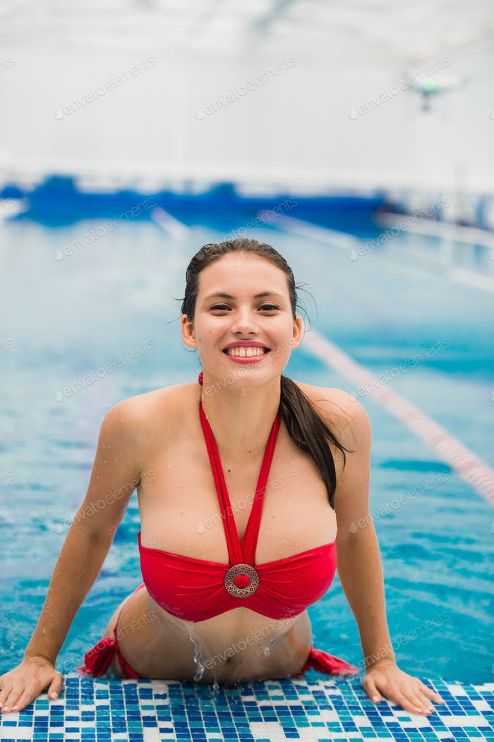 Sexy lady wearing red lingeriegetting out of the pool