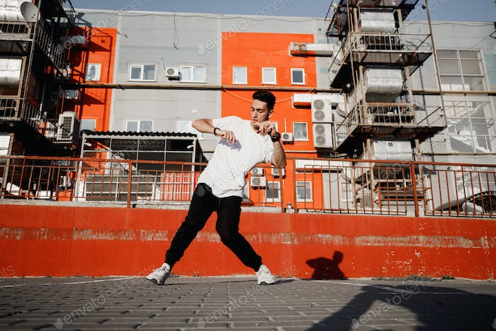 Young guy dressed in jeans and t-shirt is dancing modern dance in the street on the background of