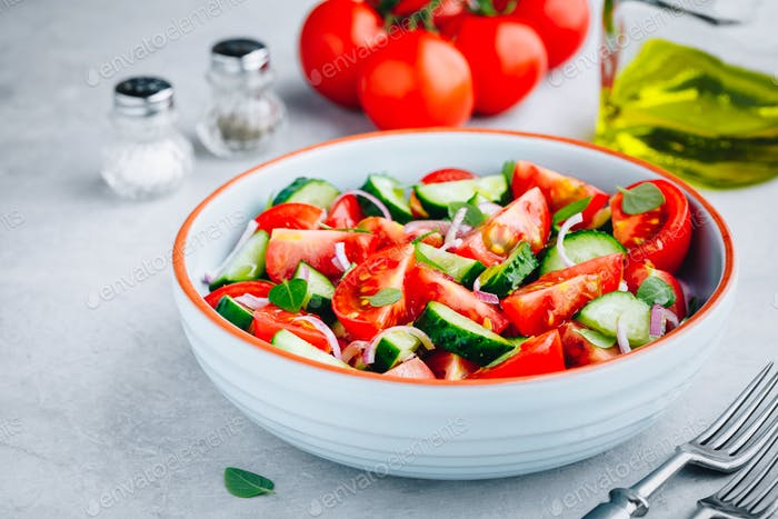 Fresh summer salad bowl with tomatoes, cucumbers, red onions, basil and olive oil dressing.