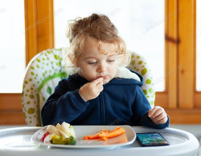 Kleinkind isst beim Ansehen von Filmen auf dem Handy.