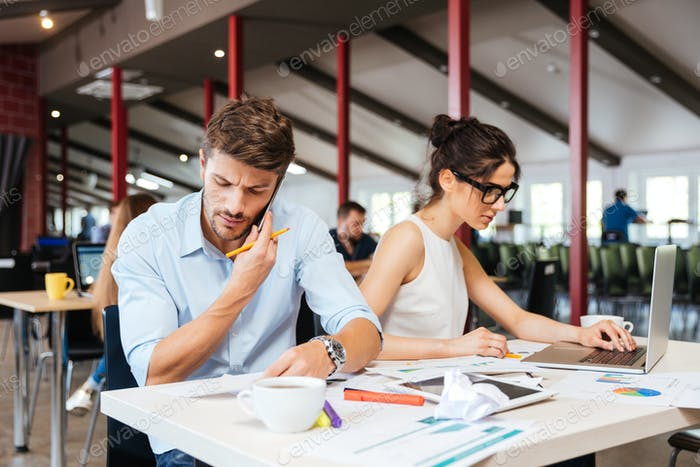 Focused young businessman and businesswoman working in office