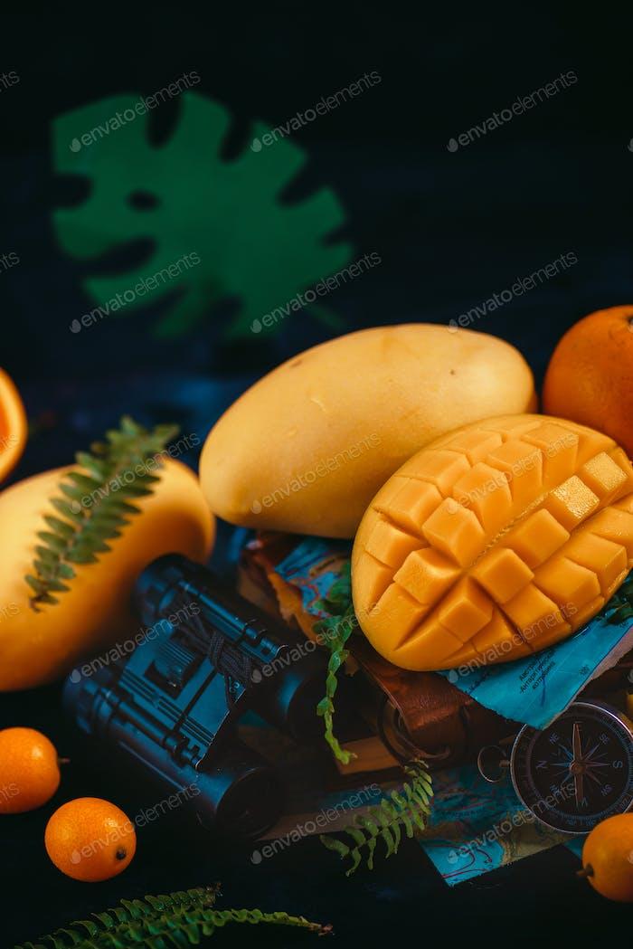 Primer plano de mango con naranjas, kumquat y otras frutas tropicales. Fondo Oscuro con espacio de copia